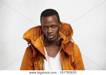 Headshot Of Serious Young African American Male Model Dressed In Stylish Orange Winter Jacket Over W