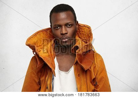 Headshot Of Attractive Confident Young Afro-american Student Wearing Trendy Winter Orange Hooded Coa