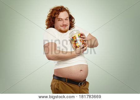 Funny Obese Young Red-haired Man With Big Belly Hanging Out His Undone Jeans Having Happy And Cheerf