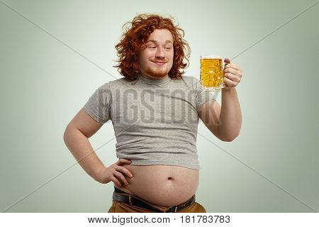 Happy Redhead Overweight Man With Big Belly Sticking Out Of His Shrunk T-shirt Holding Glass Of Cold