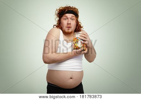 Portrait Of Startled Plump Obese Man Wearing Sports Clothing Holding Jar Of Sweets, Clasping It To H