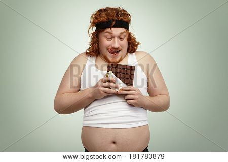 Happy Redhead Young Man In Sports Wear Holding Bar Of Chocolate, About To Have Some, Anticipating It