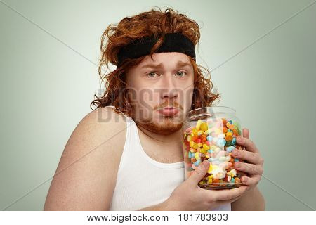 Portrait Of Unhappy Overweight Obese Young Red-haired European Man Wearing Hairband And White Tank T