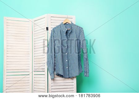 Male Shirt Hanging On Folding Screen On A Green Background