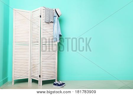 Clothes Hanging On Folding Screen On A Green Background