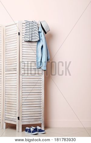 Clothes Hanging On Folding Screen On A Beige Background