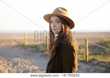 Outdoor Portrait Of Stylish Young European Woman Wearing Trendy Hat And Black Coat Looking At Camera