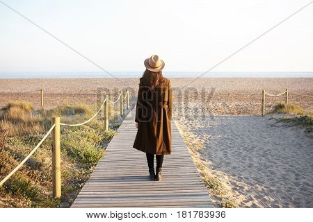 Rear View Of Fashionable Girl With Loose Dark Hair Standing Alone On Boardwalk Heading To The Sea. U