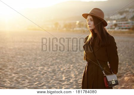 Woman On Empty Sea Beach. Young Lady With Aristocratic Traits In Stylish Outwear And Hat Standing On