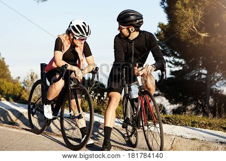 Couple On Racing Bicycles Having Rest On Their Morning Cycle Ride In Park, Both Dressed In Cycling E
