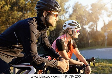 Outdoor Image Of Sporty Young European Woman And Man On Bicycles During Weekend Cycle Ride, Stopped