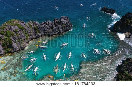A view from above on a lagoon in which boats brought tourists for a rest. Aerial view of the turquoise water between the black steep cliffs.