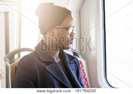 People, Lifestyle And Travel Concept. Sideview Of Handsome Dark-skinned Man In Stylish Clothing Sitt