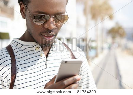 Attractive Young Afro American Traveler In Trendy Shades Using Navigation App On His Generic Mobile