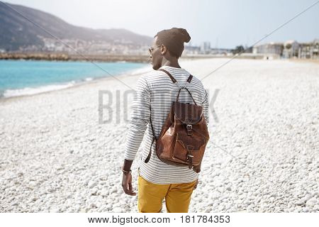Rear View Of Fashionable Black Male Student Wearing Brown Leather Backpack And Stylish Hat On Warm S