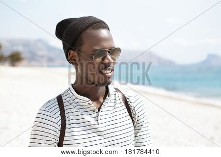 Handsome Black Hipster Wearing Stylish Hat, Sailor Shirt, Shades And Backpack Walking Alone On Urban