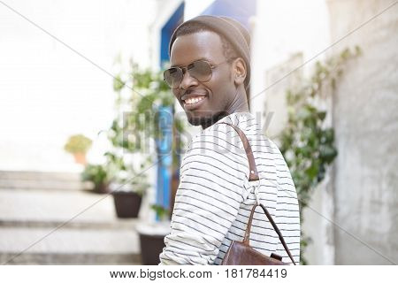 People, Lifestyle, Leisure, Tourism And Travel. Outdoor Shot Of Dark-skinned Male Student Smiling Br