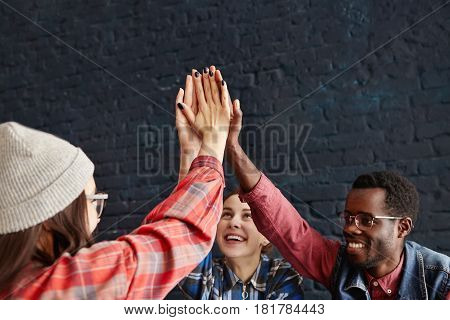 Happy Young People Giving High Five Slapping Each Others Hand In Congratulation During Meeting At Ca
