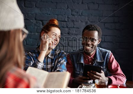 Cheerful African Man With Digital Tablet Dining At Cafe Together With His Two Female Friends: Carefr