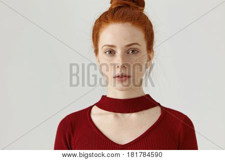 Headshot Of Fashionable Gorgeous Young Ginger Caucasian Female With Hair Bun And Freckles Dressed In