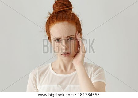 Headshot Of Unhappy Young Red-haired Female Having Frustrated And Painful Expression, Frowning, Touc
