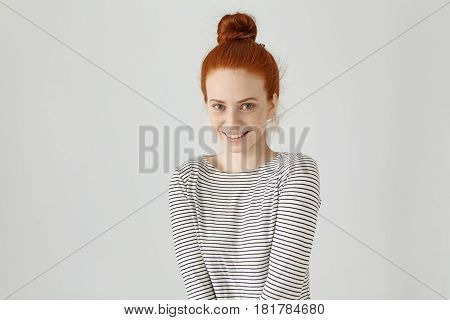 Happy Cheerful European Teenage Girl With Ginger Hair Knot Wearing Striped Long-sleeved T-shirt Look