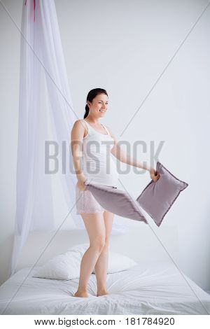 Young Pregnant Woman Throws Pillows In The Bedroom