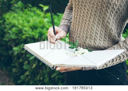 Looking up for inspiration while walking outdoor in green spring park / garden. Close-up of young woman hands writing down her hopes and dreams of future into her diary making plans. Planner To Do.
