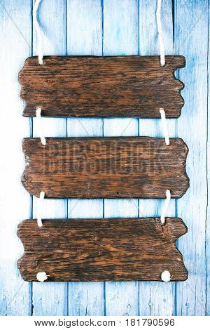 Triple signboard of natural wood on blue painted wood plank background. Space for your text and title