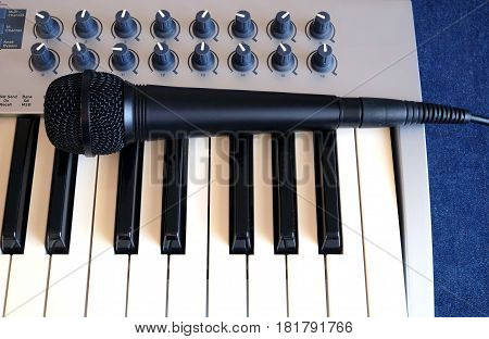 Black microphone on electronic synthesizer keyboard with many control knobs on denim background top view closeup