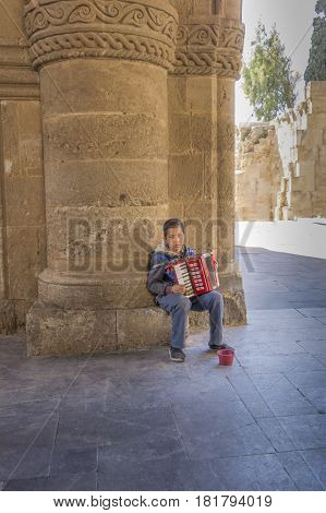 17TH FEBRUARY 2017, RHODES, GREECE - Young beggar boy playing accordian for money