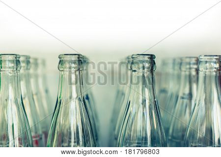 Clear glass bottles in the sun on white