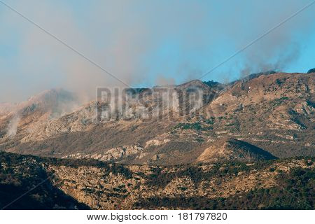 Fire in the mountains in the afternoon. Smoke over the mountains. Budva, Montenegro. Forest fires.
