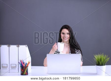 Portrait of beautiful business woman working at her desk with laptop