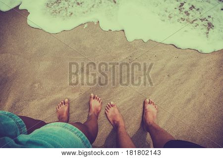 Male and female feet (couple) are standing on the sandy beach. honeymoon concept. vintage color tone style