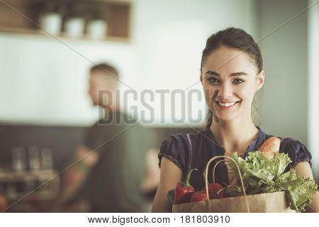 Young couple in the kitchen , woman with a bag of groceries shopping.
