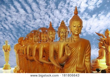 Beautiful big buddha images which be walking to rows tapered bowl in the bright sky day Wat Khao E-San Rajburi Thailand.