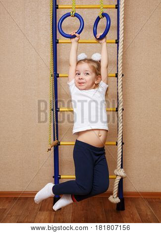 Little girl in sportswear riding a sport rings on the wall bars. The concept of a healthy lifestyle from a young age. Children sport.