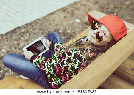 Beautiful girl sits on wooden bench in a Park with mobile tablet.
