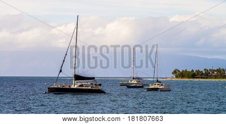 anchored sailboats jently rock on pacific waves in front of the misty molokai mountains just off lahaina maui hawaii.