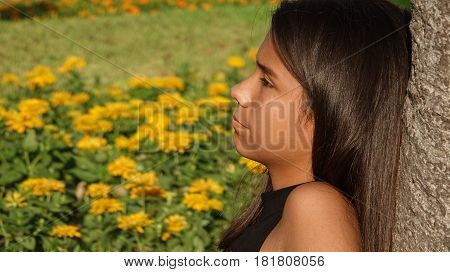 Girl In Flower Meadow Leaning Against a Tree