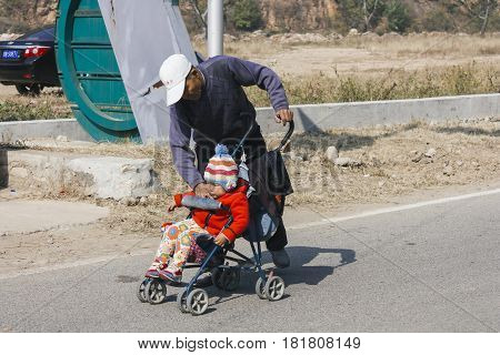 12 Oct,2014 Beijing China.  Chinese Grandpa Babysitting And Take Care Of Grandson With Baby Stroller