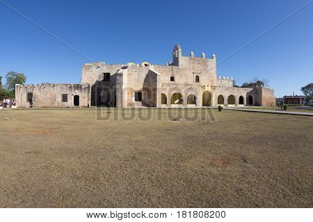 Old weathered facade and dry grass at the Convent of San Bernardino de Siena in colonial town of Valladolid in Yucatan Mexico on clear sunny day