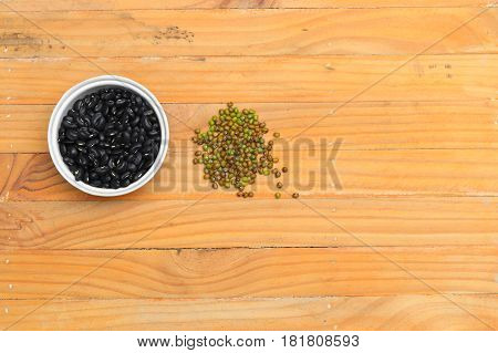 black beans in bowl and green closeup on wood floor background