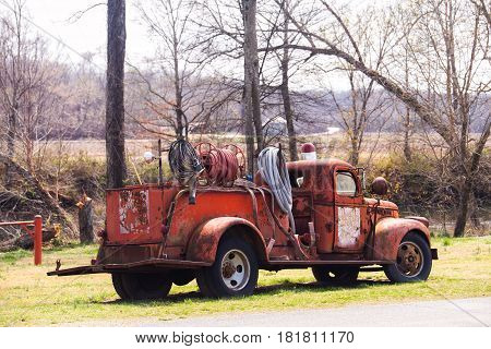 A rusted and weathered 1950s fire fighting truck loaded with hoses parked on grass with bare trees in the background