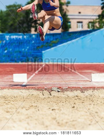 Sports competitions long jump athlete in flight