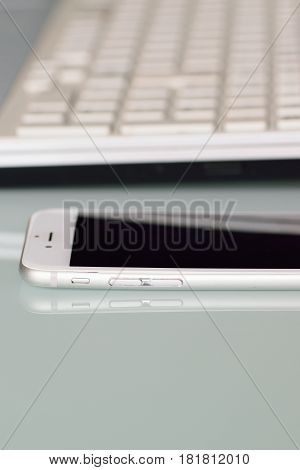 YOKOHAMA, JAPAN - APRIL 1, 2017 : Latest iPhone on desk in vertical frame with blurred laptop PC keyboard taken at Yokohama, Japan on April 1, 2017. iPhone is industry leader cellphone brand