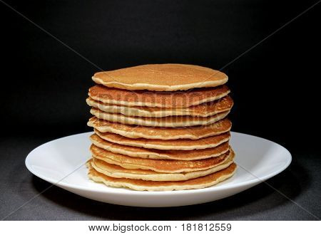 Piled up homemade plain pancakes served on white plate, isolated on black background