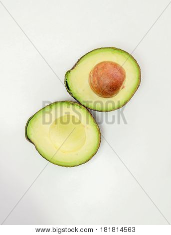 Avocado fruit isolated with green half with seed white background