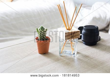 Modern workplace with tree pot and reed freshener on wooden table